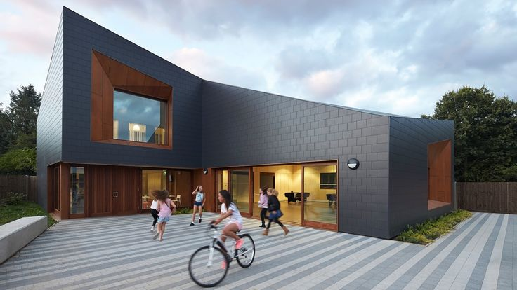 Recessed windows set into the facades of this youth centre in the English town of Tadley feature faceted timber-lined frames that contrast the building's dark fibre-cement cladding.
