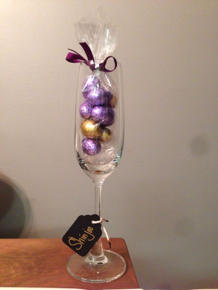 Bachelorette favors: champagne flutes with a bag of candies matching the color theme (I used purple and gold foiled chocolate eggs from Dove) and tied with matching color ribbon. Tag on the stem personalized it for guests and doubles as an identifier of which glass is yours through the night (use glass for toasts). LOVE when things can be multi-purpose!