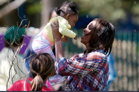"""#FirstLady Of The United States  Of America #MichelleObama holds up a baby after reading to children from the book """"My Garden"""" during the annual Easter Egg Roll on the South Lawn of the White House in Washington April 21, 2014."""