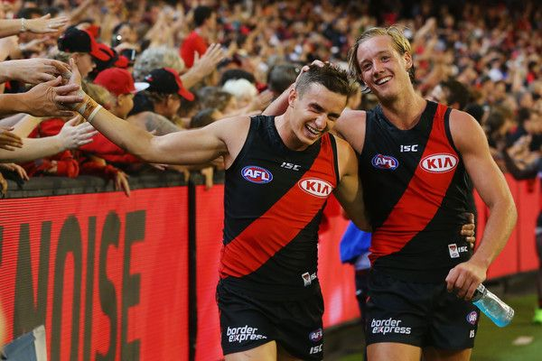 Orazio Fantasia of the Bombers (L) and Darcy Parish celebrates the win with fans during the round one AFL match between the Essendon Bombers and the Hawthorn Hawks at Melbourne Cricket Ground on March 25, 2017 in Melbourne, Australia.