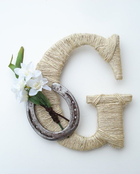 This Rustic Wrapped Letter G is decorated with a Used Horseshoe and a small bunch of flowers wrapped with a brown leather lace. You will be