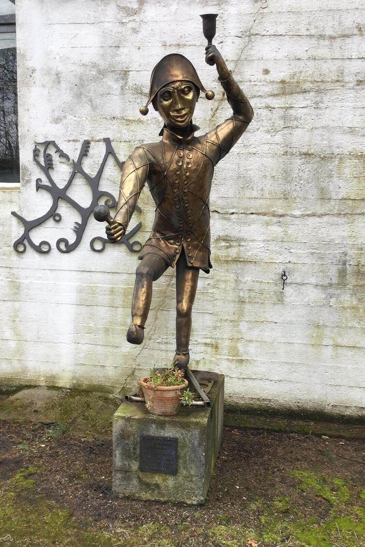 """#Trappenkamp Ein tanzender Harlekin steht vor der heute als Museum genutzten ehemaligen Schmiede des Bildhauers Alfred Schmidt. Hierbei handelt es sich gemäß der Beschilderung des Künstlers um """"August des Starken Hofnarr Fröhlich"""". Die Figur wurde aus Tombakblech geschmiedet."""