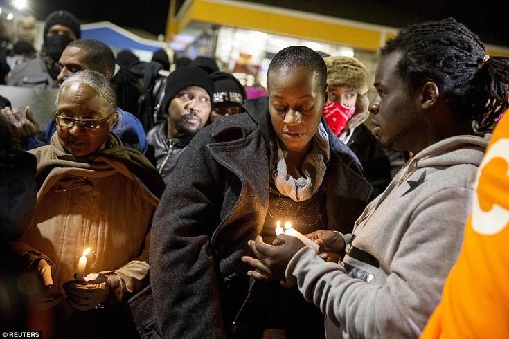 Mourning: Protests on Christmas Eve began with a candle-light prayer vigil led by Antonio Martin's mother Toni (center). About 100 people turned out to the parking lot of the Mobil gas station
