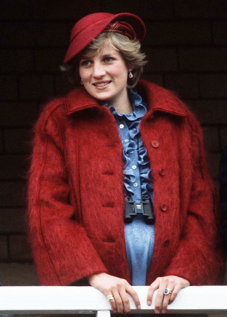 Diana, Princess of Wales is 7 months pregnant as she watches the Grand National at Aintree race course on March 31, 1984 in Liverpool, England. She is wearing red mohair coat and fashionable structured topper by John Boyd.