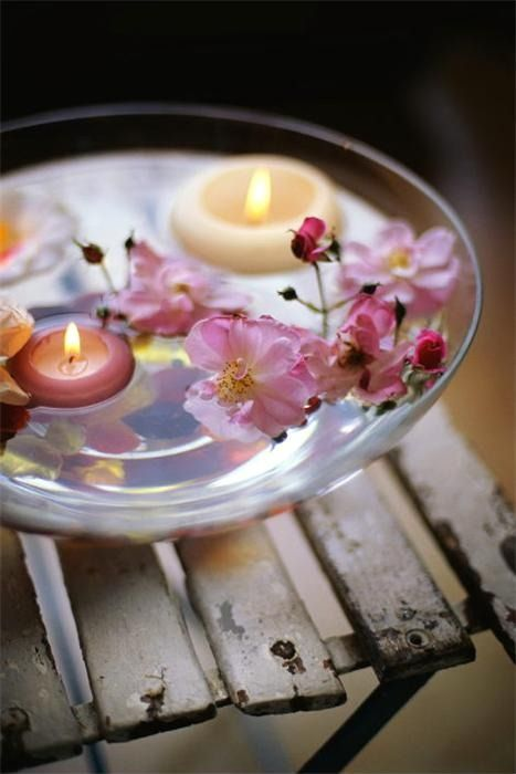 Candles and flowers floating in water in a glass bowl - summer idea for a table decor.