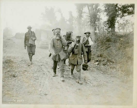"""Prisoners of war often carried the wounded. In this photo, taken during the Battle of Amiens in 1918, both the German prisoners and the Canadian wounded wear gas masks. Gas warfare became increasingly common and more dangerous as the war progressed. Wounded soldiers, often weak or unconscious, were especially vulnerable because they could not don their respirators."""