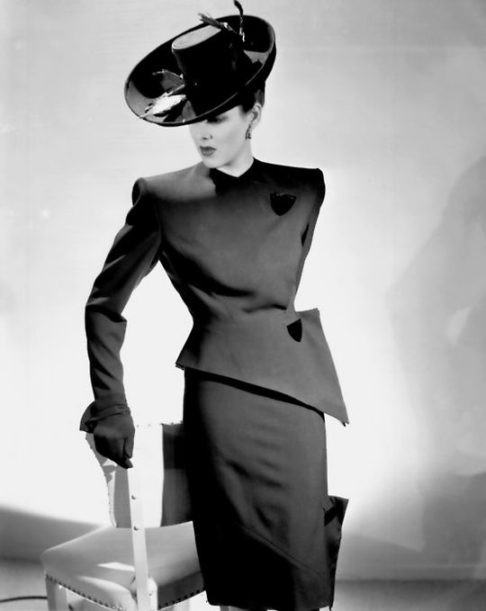 A V-line suit and hat designed by Adrian, 1944. The MGM costume designer had left MGM - where he costumed over 200 films - in 1941 to set up his own fashion house.