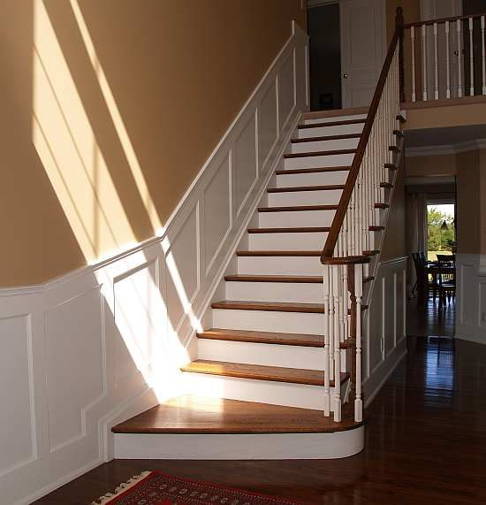 straight staircase, larger curved landing, timber brown rails and floor, white vertical and patterned half wall staircase