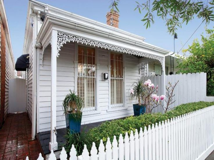 Weatherboard victorian house exterior with picket fence & hedging