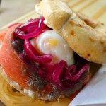 Lox da Eli: bagel artesanal tostado, salmão lox, ovo cozido cremoso, cebola roxa caramelada e cream cheese