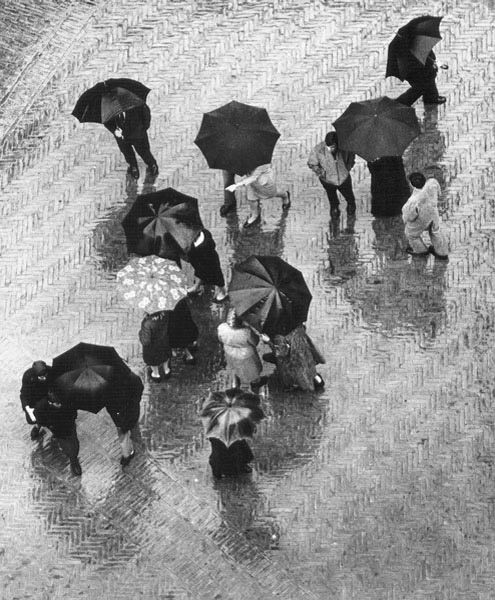 Black and white umbrellas in the rain. Wolf Suschitzky, San Gimignano, Italy, 1965