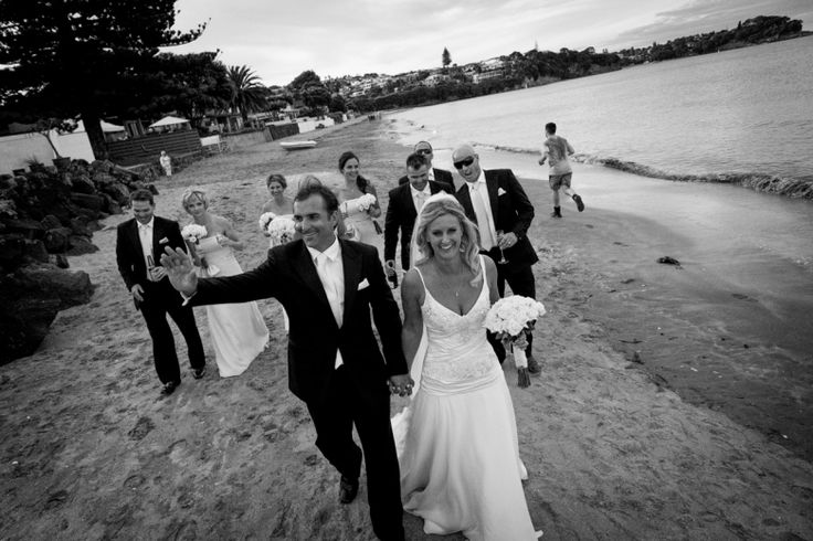 Bridal party return to the reception at a wedding at home at Milford beach, Auckland. Black and White.  beguiling fine art family photographs for the walls of the most discerning clients homes. We specialise in wedding and family portrait photography, and supply prints on the highest quality media, framed in beautiful conservation standard frames. We are a high end studio located in the beautiful city of Auckland, New Zealand.