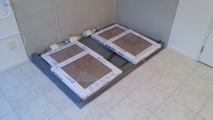 After a bit more floor levelling yesterday, the shower base is glued in place and weighted down with 130kg of tiles. 9 May 2013