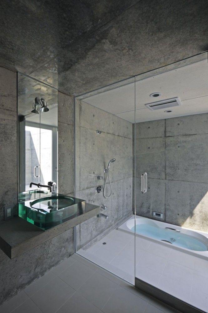 #reforma #baño con lavabo de vidrio sobre encimera de hormigón, zona de baño con ducha y bañera bajo suelo.