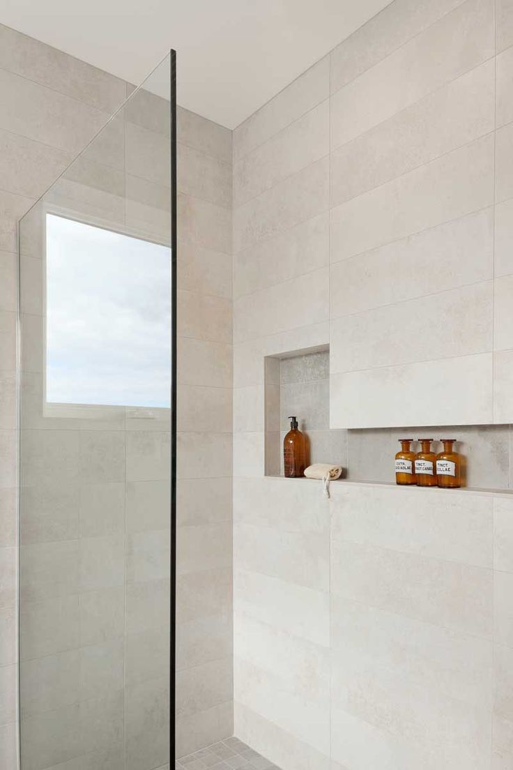 12 Design Ideas For Including Built-In Shelving In Your Shower // The built-in storage in this shower has varying heights to accommodate taller bottles.