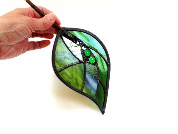This stained glass leaf suncatcher is made withtransparent emerald green glass, and wispy green glass. The leaf has a pretty textured glass in the center and glass cabochons. The leaf is surrounded with a lead came border to give it strength. It has a real branch for the stem and decorative solder. The solder lines have been treated with black patina and buffed to a pewter shine on the raised textured areas. A hanging ring with a nylon cord is attached to the back, ready for hanging in your…