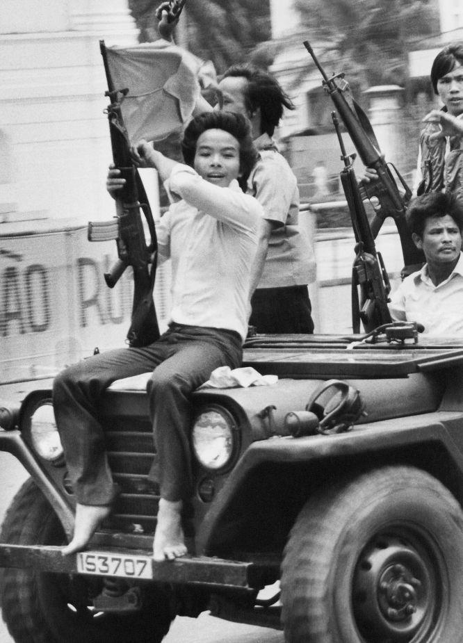 Un joven porta un arma y ondea la bandera del Gobierno Revolucionario Provisional por las calles de Saigón, 4 de mayo de 1975 by MATT FRANJOLA (AP)