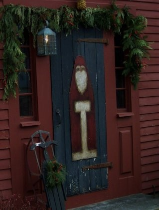 LOVE LOVE this front door scene!!!  The Santa looks amazing, and I MUST have an evergreen swag like that over MY door this winter!!!!!  ---Santa painted on an old ironing board...