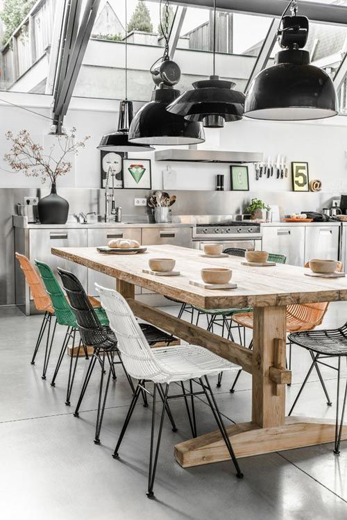 Modern rustic design: varied black hanging lights above the dining table; modern stainless steel kitchen cabinets; modern, multi-colored chairs; natural wood harvest dining table; modern art and accessories