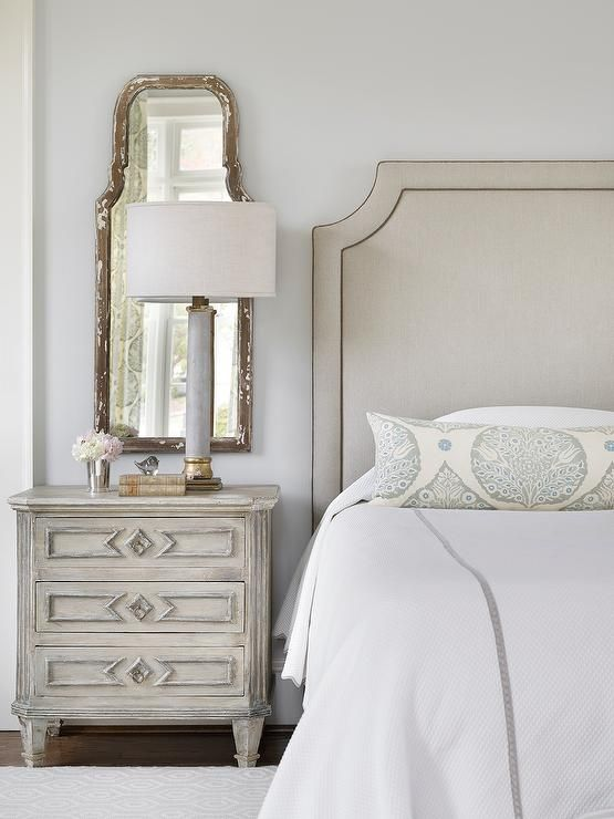 Traditional master bedroom boasts a gray headboard on bed with white and gray bedding and a gray leaf print lumbar pillow next to a gray nightstand and an alabaster lamp placed in front of a distressed gray mirror.