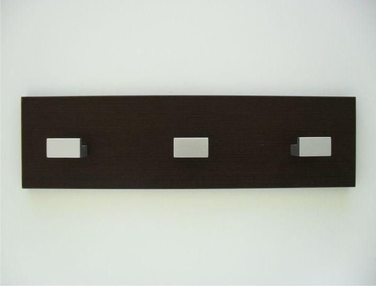 Perchero de pared moderno, fabricado en melamina wengue con tres colgadores fabricados en madera y lacados en color plata. Un perchero elegante y muy económico. Lo encontrará en www.percherosdepared.es