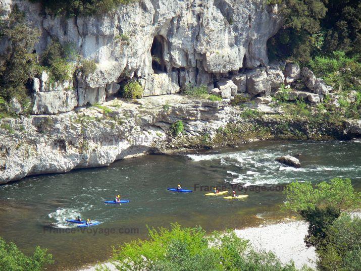 Gorges de l'Ardèche: Pratique du kayak sur les eaux de l'Ardèche ; paroi rocheuse dominant la rivière - France-Voyage.com