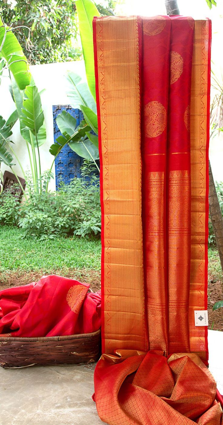 This apple red kanchivaram silk has gold zari bhuttas which combine beautifullywith the maroon thread work on the body. The border and pallu arerichly woven with gold zari making it the perfect p…