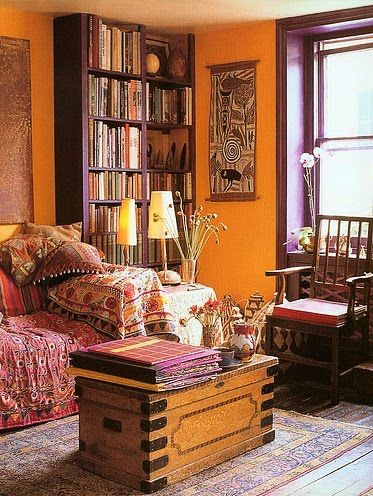 Modern bohemian living room space. The textiles on the sofa as well as the rug and the burnt sienna walls are dead giveaways that the owner has an inner gypsy spirit. :)