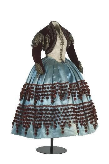 1860-65 costume combining folk and Maja elements, presented to Isabel of Bourbon, Infanta of Spain, on a trip to Valencia as a teen. Silk velvet jacket trimmed with silver and gold braid, satin skirt trimmed with maroon bobbles. CER.ES: Red Digital de Colecciones de museos de España.