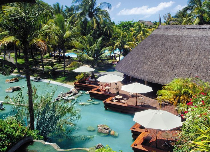 Rustic thatch and warm wooden decks with cotton cool white umbrellas create a relaxing atmosphere, the perfect barefoot luxury honeymoon location at Le Canonnier in Mauritius.