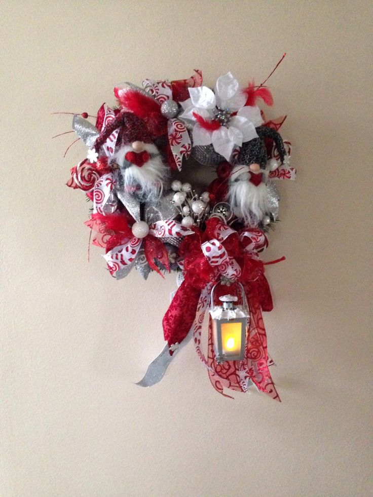 Christmas wreath.  Christmas gnome wreath. Base artificial greenery wreath. Added 6 inch deco mesh ribbon, ribbon strips and bow. One decorated lantern, christmas ornaments, poinsettia flower head, two gnomes and jingle bells, feathers.  More at https://www.facebook.com/Moje-vence-995508700482994/