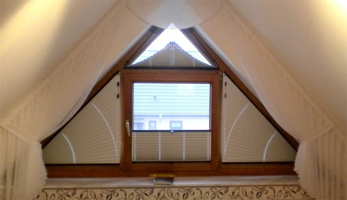 living room curtains ideas, gable window seen in close up, with wooden framing, cream colored blinds, and gathered semi-sheer curtains in the same color