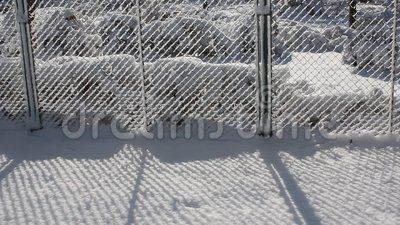 Winter scene in park near a fence covered by snow.