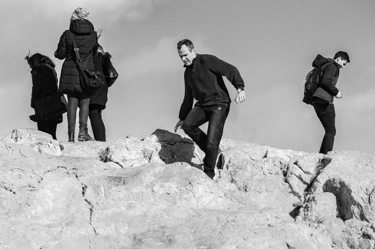 A man is climbing down a rock cautiously, so as not to slip and fall. A photo taken on top of Areopagus which is an excellent place to shoot people!