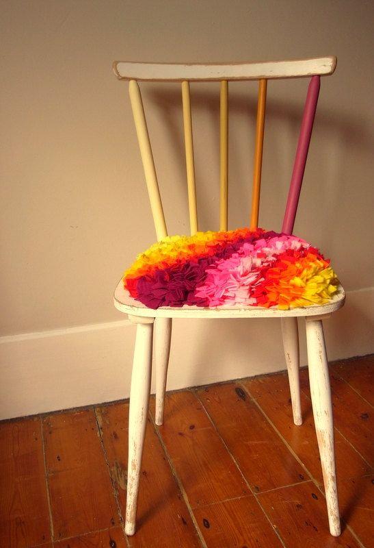 Colour By Numbers Chair by OhBoxinghare on Etsy, £55.00. Hundreds of felt offcuts have been individually threaded through a hessian base to create a tufty rug cushion providing softness to the simple chair with rainbow rails.