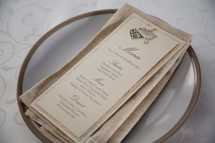 Silver bird charm ivory wedding menu with textured paper detail. Bird and cage menu. Styling by Jani Venter. Photo by Rikki Hibbert.
