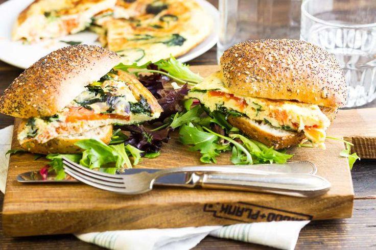 Recept voor frittata van gerookte zalm, geitenkaas en spinazie voor 4 personen. Met zout, olijfolie, peper, geitenkaas, gerookte zalmfilet, spinazie, romatomaat, ei, melk, rode ui en kampioentje