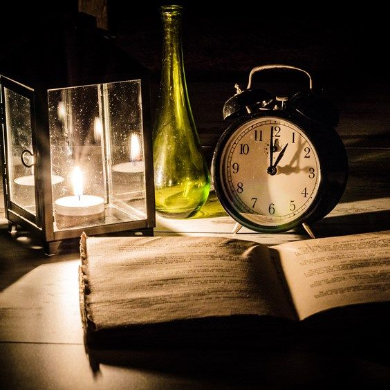 Vintage book, candle lamp, green bottle and clock