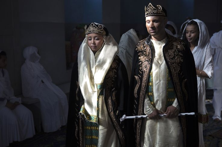 A traditional Eritrean wedding outfit includes a crown made from dark velvet and a purple dress with gold embroidery. The bride's costume compliments that of the groom.