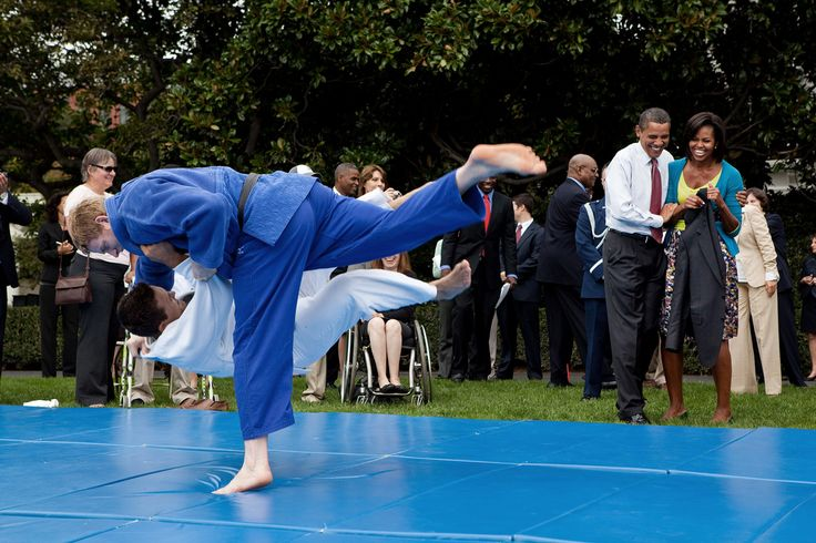 President Barack Obama and First Lady Michelle Obama watch Olympian Ryan Reser, in white,