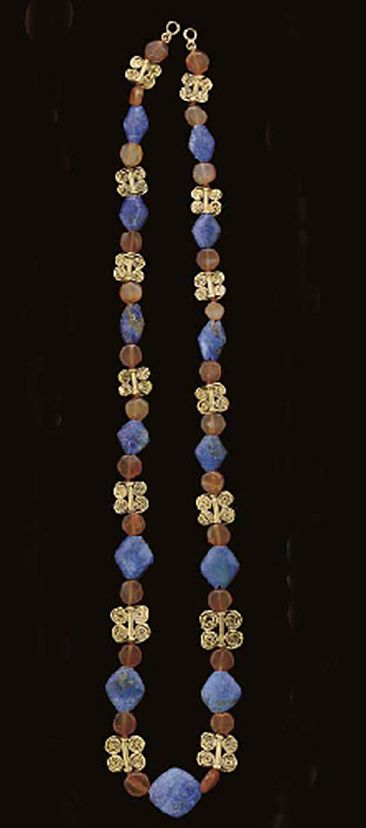 A WESTERN ASIATIC GOLD AND CARNELIAN BEAD NECKLACE   Circa 2nd Millennium B.C.   Including fourteen gold quadruple spiral beads, each with a central tube joined to two double-spiraling wires, together with thirteen rhomboidal modern lapis lazuli beads, and twenty-six disk-shaped carnelian beads