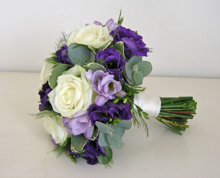 ivory roses purple lisianthus, lilac freesia, mixed greens. would be a beautiful brides bouqet