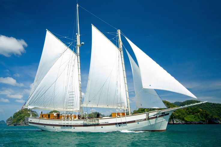 A refurbished schooner reminiscent of ancient ships, sailing among the tropical islands of Indonesia.