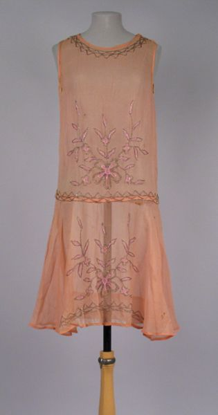 Dress Accession Number: 2005.55.2-A-C Date Made: 1920s Description: Dress; peach crepe with beaded floral design, sleeves detached. Beaded floral design at waist, front and back, and on front of skirt. Beaded design in pink and gray beads. Sleeveless dress has a scoop neckline. Neckline is accented with gray beads in a zig zag pattern. The same zig zag design encircles the drop waist and accents a portion of the bottom hem.