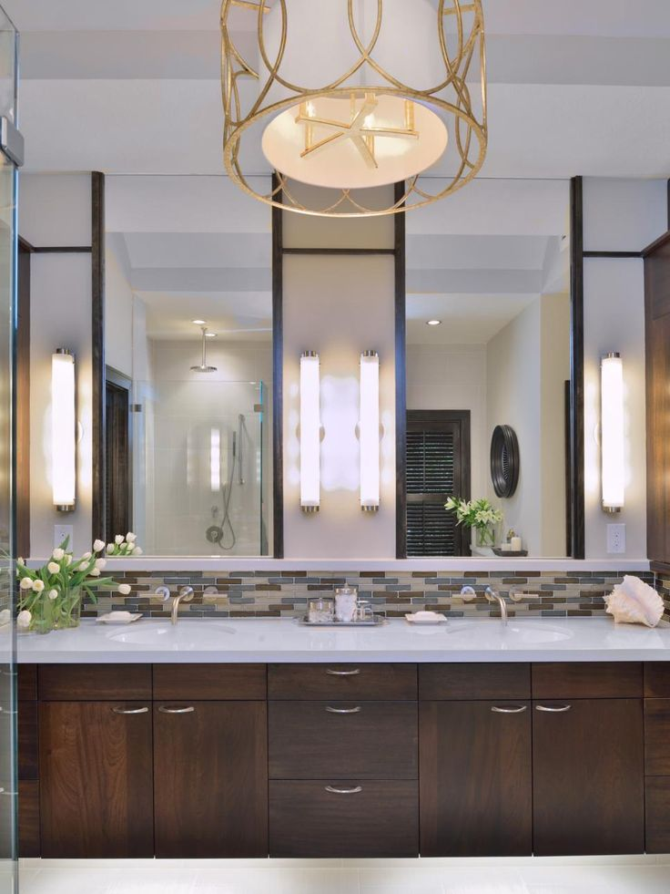 The clean lines of this modern bathroom include an an earth-toned mosaic tile backsplash above the dark brown double vanity. An artistic modern drum pendant light provides illumination and serves as a focal point.