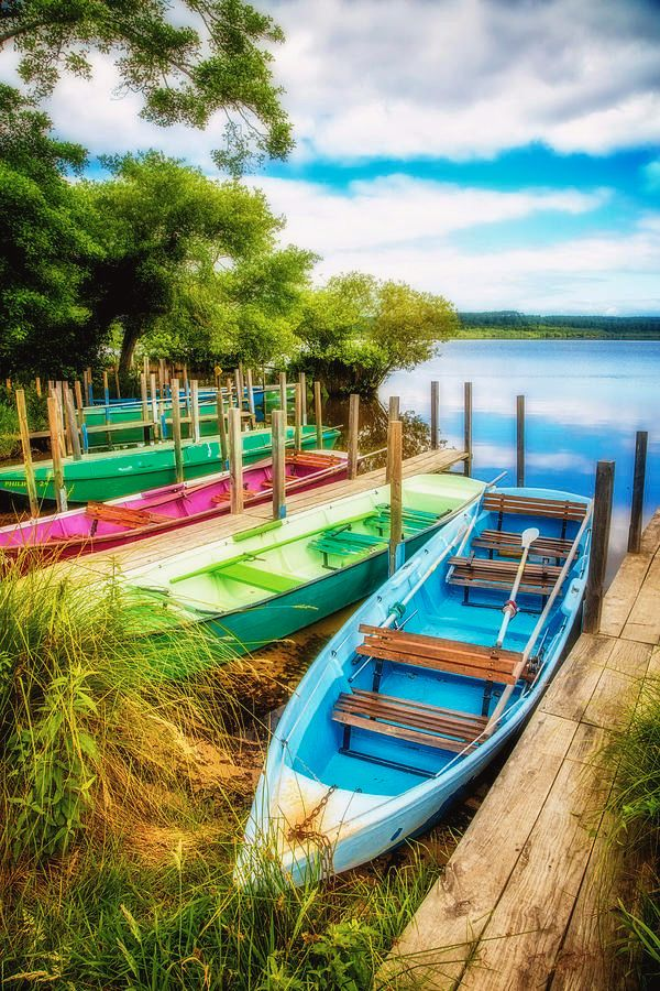 Summer Colors is a photograph by Debra and Dave Vanderlaan. A group of very colorful rowboats waits for the summer to begin! The lake is so pretty,  big puffy clouds overhead with touches of blue reflecting in the clear clean water. This gorgeous scene was captured on the edge of a big lake in southwestern France, very close to the coastline and the ocean beyond. Source fineartamerica.com