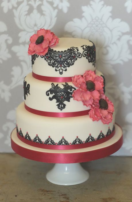 "The intricate black sugar lace with piped accents in magenta give this petite wedding cake a slightly decadent feel.  Blousey sugar anemones in a matching hot pink colour with black centres add the finishing touch.   As seen: 6"", 8"" and 10"" tiers."