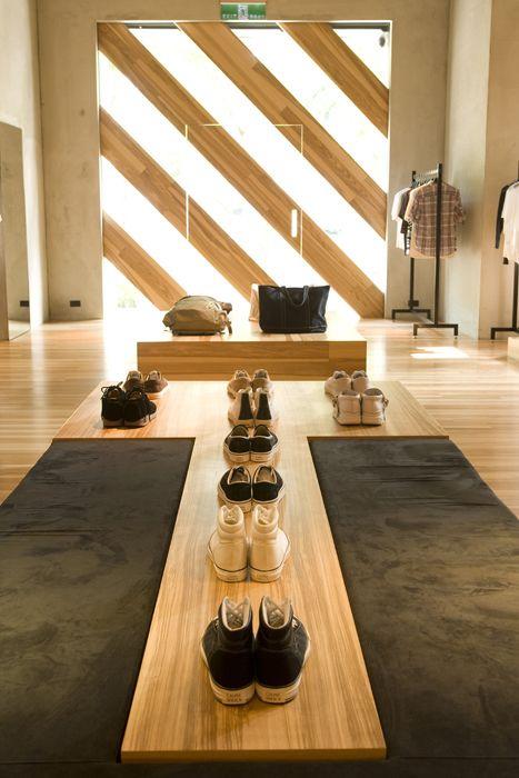 Me gusta la pared del fondo, rayada con madera e iluminacion, tiene un diseño muy creativo y chic. También es interesante la mesa alargada centrada y la posición de los zapatos en ella tan simétrica