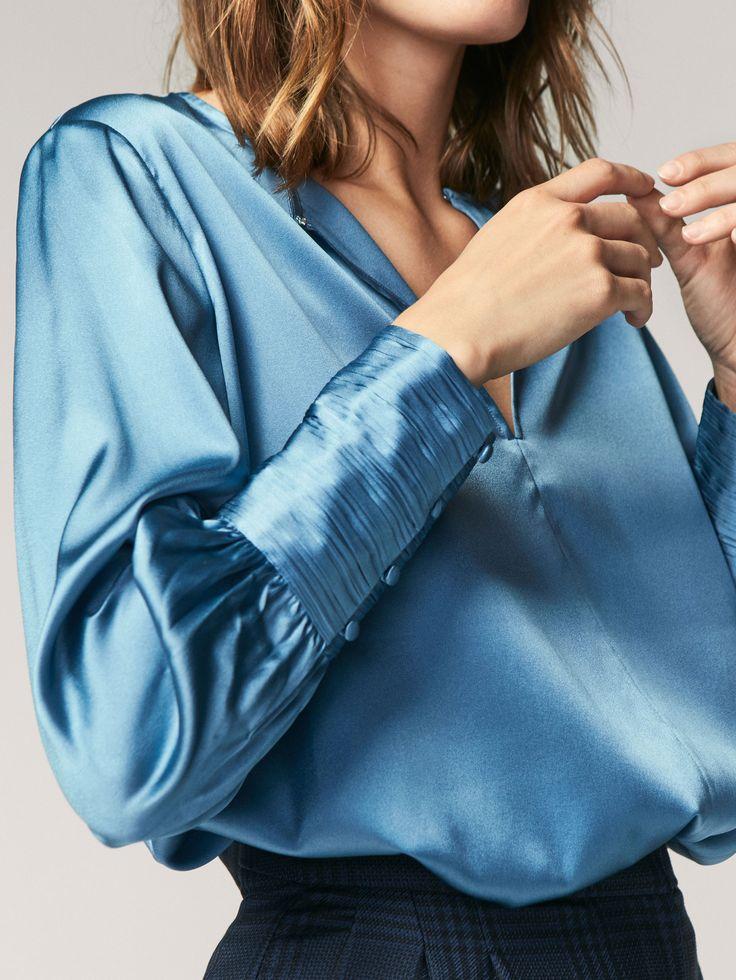Camisa fluida, confeccionada en tejido de seda morera. Corte recto, cuello redondo, cierre de un corchete, manga larga terminada en puño abotonado plisado y bajo redondeado con aberturas laterales.