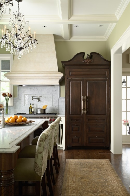 The beautiful custom refrigerator cabinet is one of Simmons' favorite features. This piece is a replica of a 1780s armoire with hand-carved detailing. Simmons found cast bronze pulls with acorn finials to put on the front of this fully functional refrigerator.